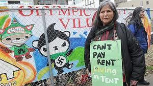 """Nativo Canadense exibe uma placa """"Não posso pagar aluguel, vivo em uma tenda"""", em frente à Vila Olímpica em Vancouver"""