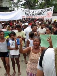 Uma moradora se emociona diante da ameaça de seu despejo. Ao fundo, moradores e militantes defendem a entrada da comunidade. Foto: Patrick Granja