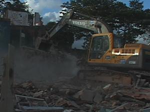 A backhoe striking at a home amid rubble and dust