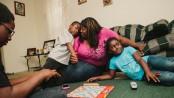 Stacey Calvin joga Scrabble  com seus três  filhos, Jayde, 6, Jaela, 9 e Jevon, 12, em seu apartamento em Stone Mountain, Geórgia. Foto por David Walter Banks para o The New York Times