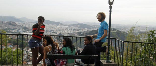 Músico britânico Tom Ashe passa tempo com seus alunos perto da casa que aluga na comunidade Pereira da Silva no Rio de Janeiro. Para muitos gringos de baixa renda, as favelas são os únicos lares a preços acessíveis enquanto o restante do mercado imobiliário está em alta. (Pilar Olivares/Reuters)