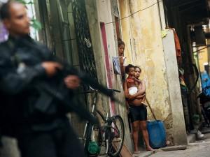 Moradores observam policiais militares na Maré, um dos maiores complexos de favelas do Rio de Janeiro, no dia 30 de março. Em um dos países mais violentos do mundo, o número de assassinatos abaixou, mas só para os brancos.