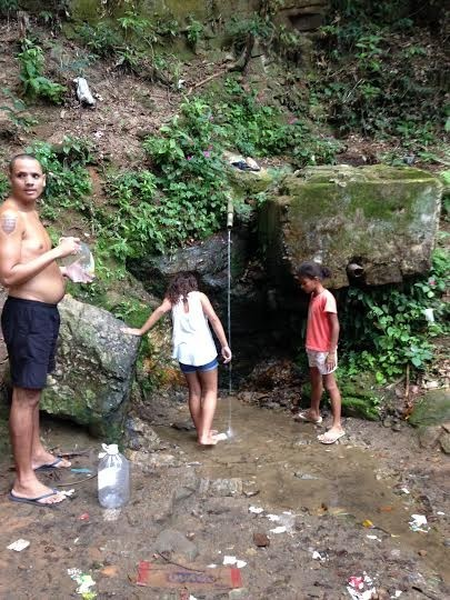 """A """"fonte"""", ou chafariz, de água potável localizada na floresta que fica atrás da comunidade da Rocinha Vila Laboriaux. Com os serviços de água irregulares e a água natural sendo vista como mais saudável que a água da cidade, os moradores fazem a caminhada para a floresta carregando sacos ou recipientes para trazer de volta a água para suas casas."""