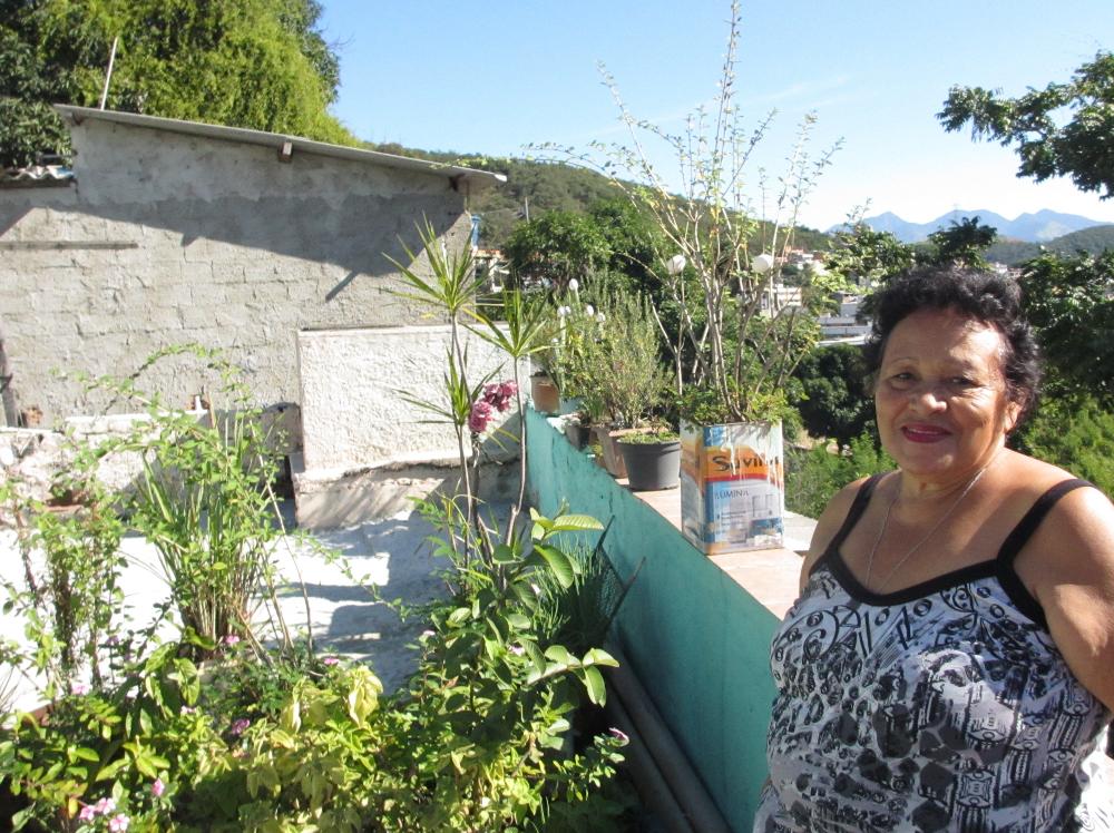 Dona Maria do Carmo ao lado de seu jardim