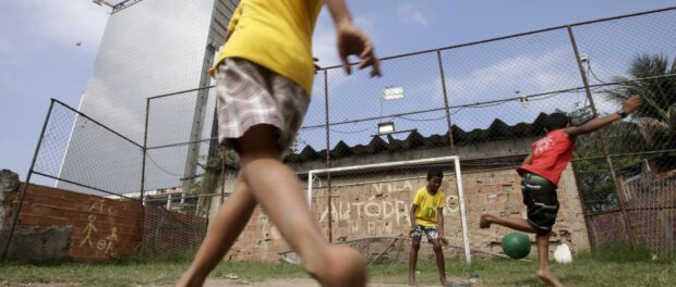 Children play soccer in the Vila Autodromo slum in Rio de Janeiro, Brazil, July 28, 2015. As sports arenas rise up around them and neighbours' houses are demolished, around 50 families remain in Vila Autodromo, a favela bordering the Olympic Park in Rio de Janeiro. About half of those refuse to leave the favela, which they describe as