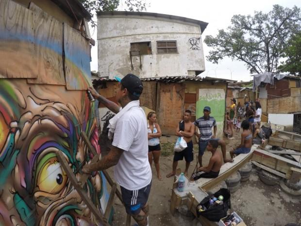 Grafiteiro Bruno Smoky da favela Brasilândia em São Paulo contribui para a obra de arte na mais nova favela da Maré. Foto por Monara Barreto, 14 de março de 2014.