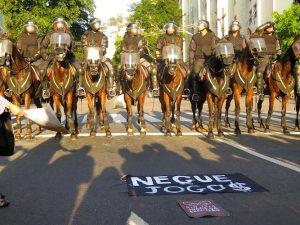 Mulher coloca um cartaz na frente da cavalaria da polícia