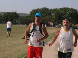 Edivandro corre na Vila Olímpica da Maré com um professor assistente e uma mochila de equipamentos.