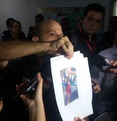 Capitão Zuma, comandante da UPP de Nova Brasília, exibe fotos de traficantes armados.