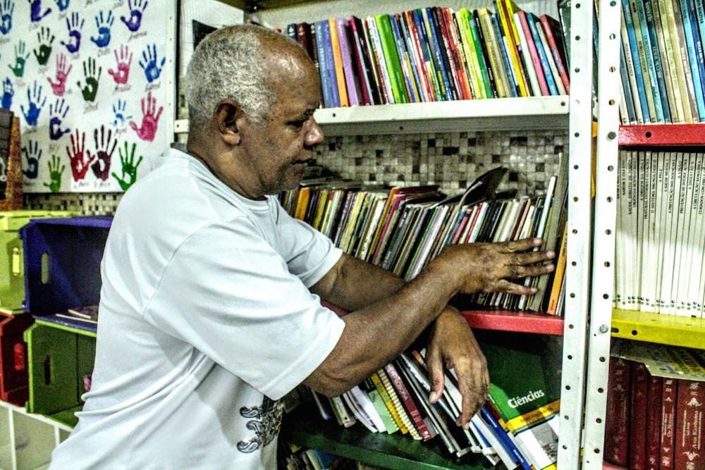Paulo cuida da biblioteca. Foto por Hector Santos| Raízes em Movimento