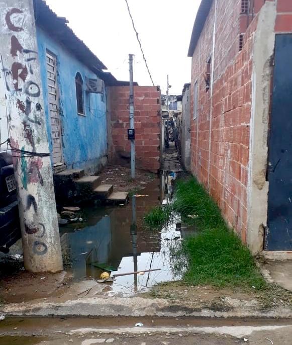 Esgoto a céu aberto na porta de uma casa e um adolescente tendo contato. Foto por Moana Couto e Rayane Marques
