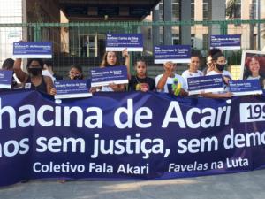 Mães, pais e ativistas de favelas vítimas de violência do Estado seguram placas de rua com os nomes dos 11 jovens desaparecidos na Chacina de Acari.
