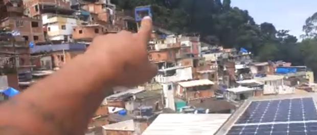 Placas solares do Insolar Santa Marta na associação de moradores da favela mostradas por Veronica Moura e Leo Elétrica (cujo braço aparece na foto).