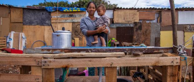 Mãe e filho na frente da cozinha improvisada montada na ocupação Jardim Julieta na Vila Medeiros, Zona Norte de São Paulo. Foto por: Léu Britto.