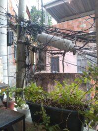 Emaranhado de fios em um tronco de árvore usado como poste bem próximo à casa de moradores, no Morro do Sereno, representa risco de incêndios e choques. Foto por Karina Figueiredo