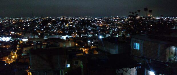 Zona Norte do Rio vista do alto do Morro do Sereno à noite, com algumas casas de moradores em primeiro plano. Foto por Karina Figueiredo