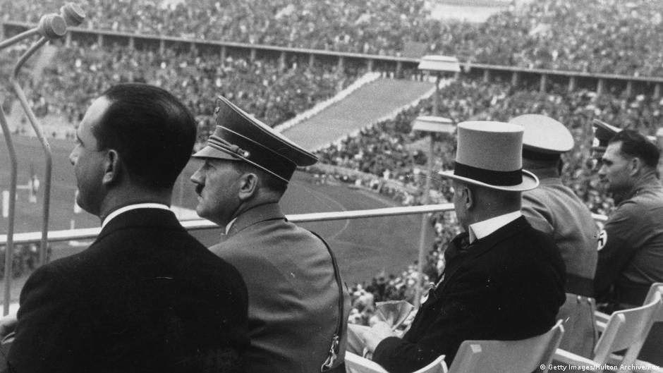 Adolf Hitler assista as competições no Estádio Olímpico de Berlim, em 1936, na Alemanha Nazista, ao lado do príncipe da coroa italiana.