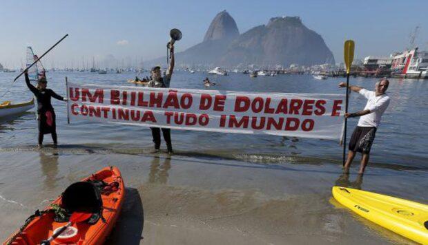 Biólogo Mario Moscatelli, com um megafone, protesta com atletas e ativistas diante da poluída Baía de Guanabara, palco de competições olímpicas. Foto por: Sergio Moraes/Reuters