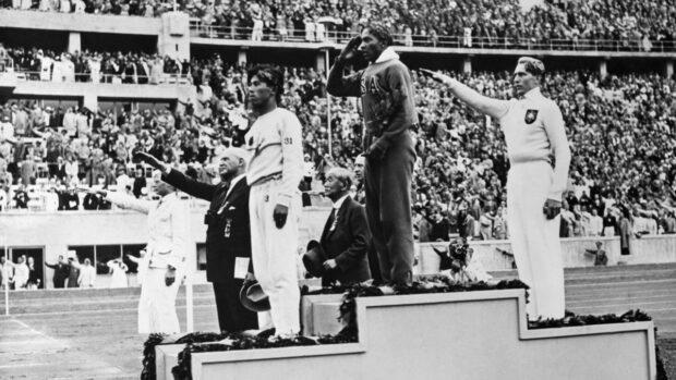 Naoto Tajima, medalhista de bronze (à esquerda), Jesse Owens, medalhista de ouro (no centro), e Luz Long, alemão medalhista de prata (à direita), fazendo a saudação nazista, durante a Olimpíada de Berlim de 1936, na Alemanha nazista. Hitler assistiu a competição no Estádio Olímpico, mas deixou o local para não testemunhar a cerimônia da premiação da vitória negra sobre os arianos em Berlim