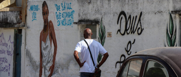 """O pai de Kathlen Romeu a observa em uma pintura momentos antes do ato inter-religioso que marcou os 7 dias. No muro, a frase """"Que sua luz guie os caminhos da nossa luta!"""""""