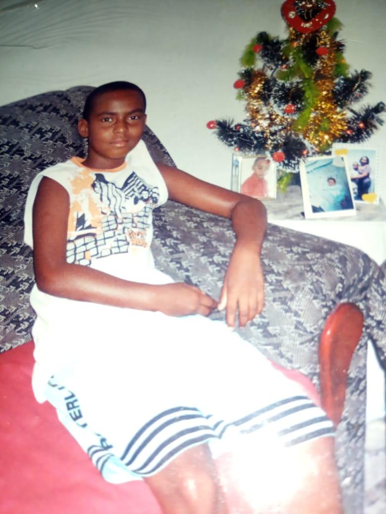 Cleyton Santanna ainda criança, sentado no sofá da sala de sua casa. Arquivo pessoal de Cleyton Santanna