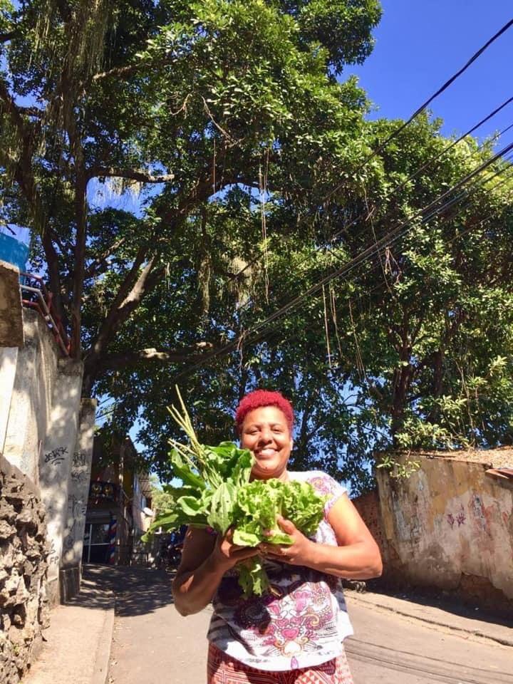 Tânia Cristina com suas hortaliças em mãos depois de um encontro com as erveiras. Foto por: Marcelo da Paz